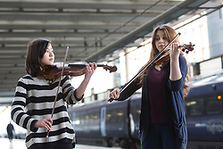 © Licensed to London News Pictures. 01/03/2016. London, UK. Two exceptional teenage violin prodigies, Coco Tomita, 13 and Louisa Staples, 15, who are competitors in the world's leading competition for young violinists, the Menuhin Competition London 2016 (which takes place on 7-17 April 2016), surprise commuters as they perform on the platform at St Pancras International Station in London. Photo credit : Vickie Flores/LNP