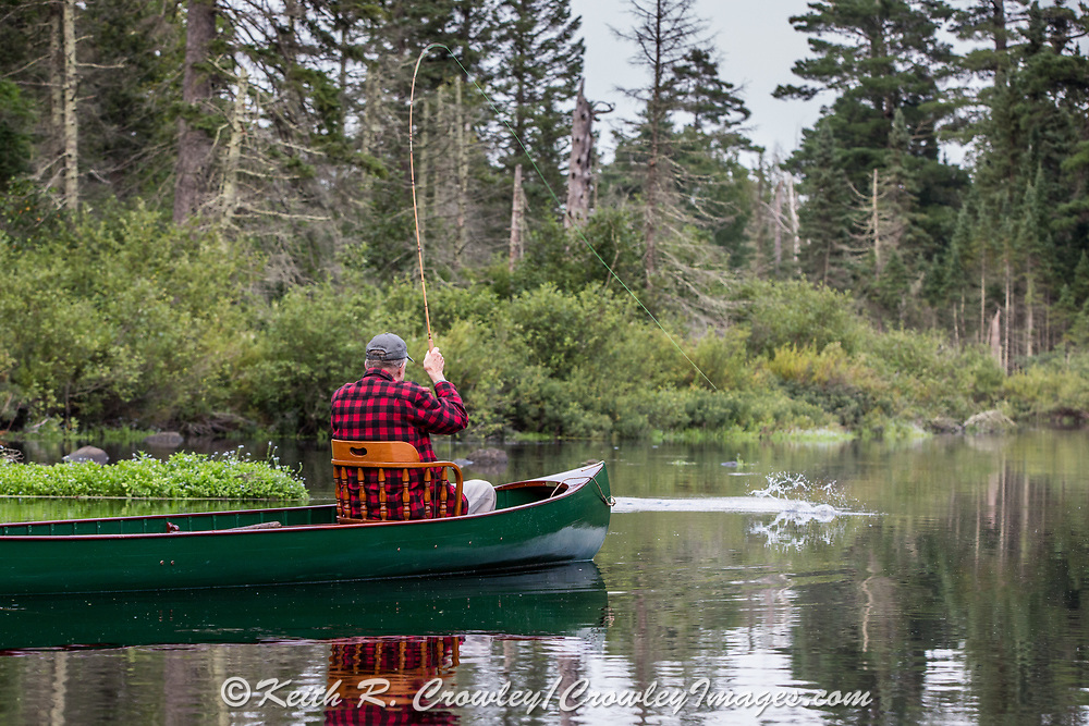 Angler Matson Holbrook fights a native Brook trout in the Upper Brule River near Lake Nebagamon, Wisconsin, from the bow seat of a 1895 Lucius guide canoe meticulously restored over the course of two years by Brule Guide Damian Wilmot.