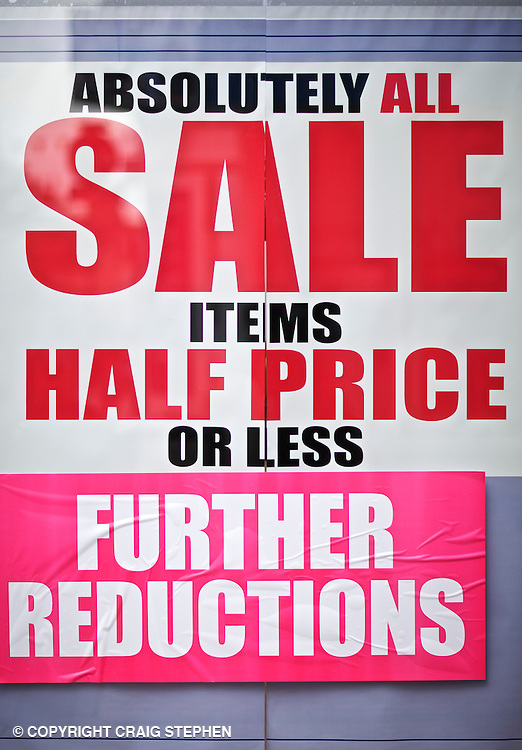 Promotional poster advertisng sale, money off, clearance items, reductions, buy one get one free in High Street shop windows in Scotland, UK