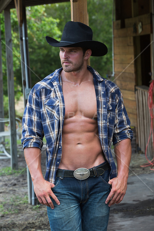 sweaty muscular cowboy with an open shirt walking on a ranch with a saddle in his hand