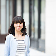 Portrait of an attractive mid adult woman in urban street. Asian female in her 30's looking to camera.