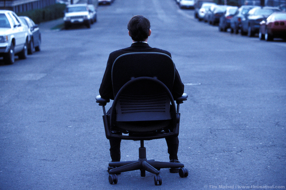 Man and office chair in the street