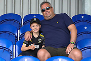 Young AFC Wimbledon fan with adult male (man) with hand on his shoulder during the EFL Sky Bet League 1 match between AFC Wimbledon and Wycombe Wanderers at the Cherry Red Records Stadium, Kingston, England on 31 August 2019.