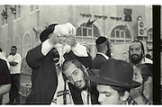 Vintage image of Saying The Kaparot prayer. Mea Shearim, Jerusalem, Israel<br /> Kaparot, an aged old Jewish tradition were a chicken is waved over the believer?s head, reliving the person from all sins which are passed on to the chicken. The chicken is slaughtered and at times given to charity.<br /> Black and white grainy image
