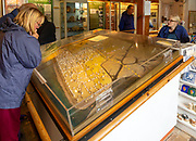 People examine model of lost city inside Dunwich museum, Suffolk, England, UK