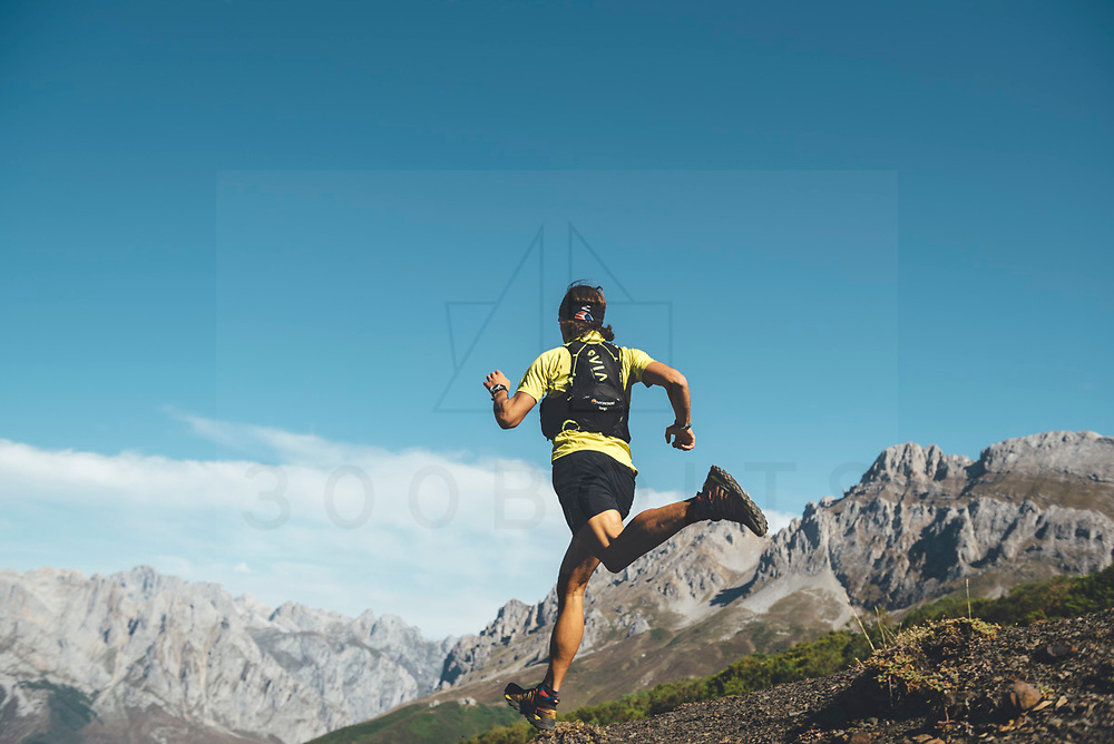 Trail runner jumping downhill in Collado Jermoso, Leon, Spain Trail runner running uphill in Collado Jermoso, Picos de Europa National Park, Spain