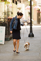 A young woman walks her English bulldog through Trounce Alley in downtown Victoria.  Victoria, Vancouver Island, British Columbia, Canada.