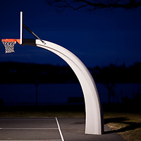 A spot light shinning on the basketball rim in an outdoor park in Rumson New Jersey