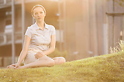 Thoughtful young businesswoman sitting on office lawn