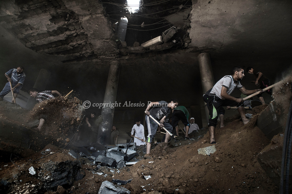 Gaza Strip, Gaza City: Palestinians are seen as they remove the rubble in Martyr Imam Hassan al-banna mosque in Zeitoun neighbourhood, following an overnight Israeli airstrike on August 9, 2012. ALESSIO ROMENZI