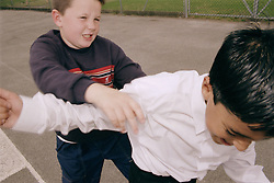 Two primary school boys fighting in playground,