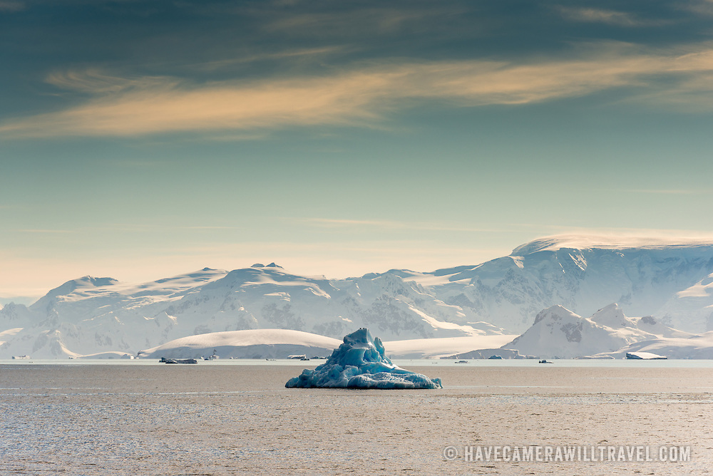 A blue iceberg floats in the foreground, with some of the dramatic landscape of the Gerlache Strait in the background.