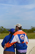 South Merrick, New York, USA. 24th May 2015. At Levy Park & Preserve, a young man, wearing a Mets baseball jacket, and a woman have their arms around each other as they face south toward the sky over Jones Beach where planes performed in the Bethpage New York Air Show. Many visitors watched the air show from the marshland park after area parkways to the famous Long Island beach were closed when it filled to capacity.