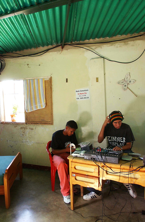 """Davis Semeco, righ, plays music  on """"A New Day Radio"""", a community radio station in Caracas, as his friend Edgar Russian listens.  The station operates out of the home of  Zulay Zerpa,  who donates the space in her bedroom 7 days a week between 3pm and 9pm.   Chavez and his government have been increasingly supportive of these generally Chavista community media stations as a response to the anti-chavista private media."""