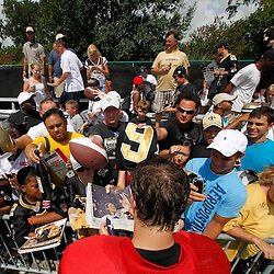 July 29, 2011; Metairie, LA, USA; New Orleans Saints quarterback Drew Brees (9) signs autographs for fans following the first day of training camp at the New Orleans Saints practice facility. Mandatory Credit: Derick E. Hingle