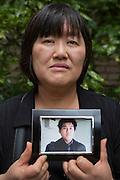 Mieko Kogawa med ett fotografi av sin son Kazunori Kogawa som genom överdriven övertidsarbete och trakasserier av chefen drevs till självmord på restaurangen han jobbade. Tokyo, Japan