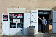 Patron Didier Lambert at discount wine merchants vigneron shop in rue Guadet Saint Emilion, Bordeaux wine region of France