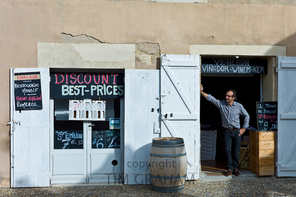 Patron Didier Lambert at discount wine merchants vigneron shop in rue Guadet Saint Emilion, Bordeaux wine region of France