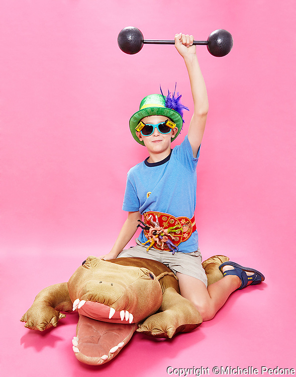 Tween boy wearing a green top hat trix 400 sunglass and a  mexican wrestler belt sitting on stuffed aligator holding up a bar bell. Photographed at the Photoville Photo Booth September 20, 2015