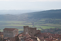 Italian landscape:view of Massa Marttima in Tuscany, historic town center with roofs and green Maremma's hills on misty background in winter season