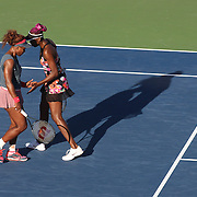 Serena Williams, USA, (left) and Venus Williams, USA, in action in the late afternoon light on Louis Armstrong Stadium against Anastasia Pavlyuchenkova, Russia and Lucie Safarova, Czech Republic, in the Women's Doubles, Round 3 match at the US Open. Flushing. New York, USA. 4th September 2013. Photo Tim Clayton