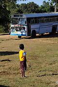 A young boy watches as another bus carrying returning displaced people arrives at a transit centre in northern Sri Lanka. UKaid funding is helping the International Organisation for Migration to provide transport home for thousands of displaced people.<br /> <br /> To find out more about how DFID is helping in Sri Lanka, please visit www.dfid.gov.uk ( http://www.dfid.gov.uk ) <br /> <br /> Image: Russell Watkins / Department for International Development