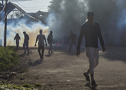 April 13, 2018 - Srinagar, Jammu And Kashmir, India - Kashmiri Muslim protesters throws stone towards them during a protest in Srinagar, the summer capital of Indian administered Kashmir, India,  against the recent civilian killings in valley and the gang rape and murder of a eight year old Muslim girl in Kathua district of Jammu region. Youths clashed with Indian forces as protests were held at several places in Srinagar on Friday after congregational Friday prayers in Srinagar. (Credit Image: © Masrat Zahra/SOPA Images via ZUMA Wire)
