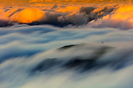 Patches of moving clouds among the mountain ridge at sunset