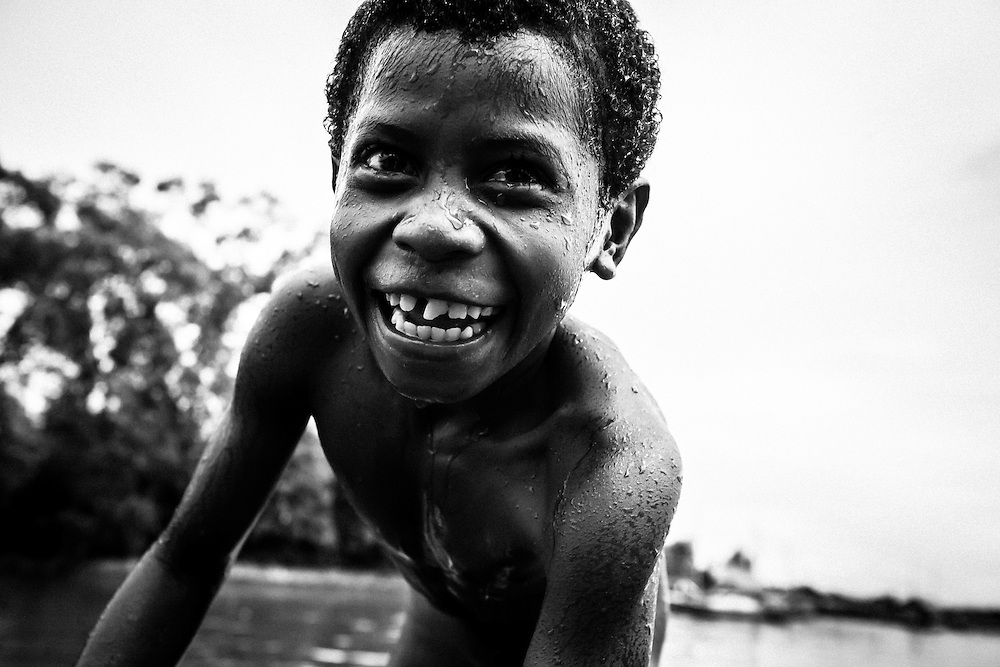 Where: Papua New Guinea.<br /> <br /> All the shot is about is a child enjoying the simple fun of jumping into the ocean. <br /> What a great smile.
