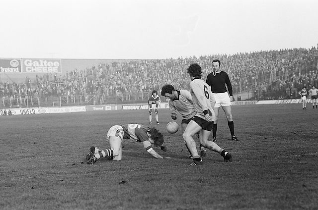 Kerry falls to the ground after a tackle as the referee and two Dublin players stand over him during the All Ireland Senior Gaelic Football Semi Final, Dublin v Kerry in Croke Park on the 23rd of January 1977. Dublin 3-12 Kerry 1-13.
