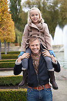Portrait of father carrying daughter on his shoulders at park