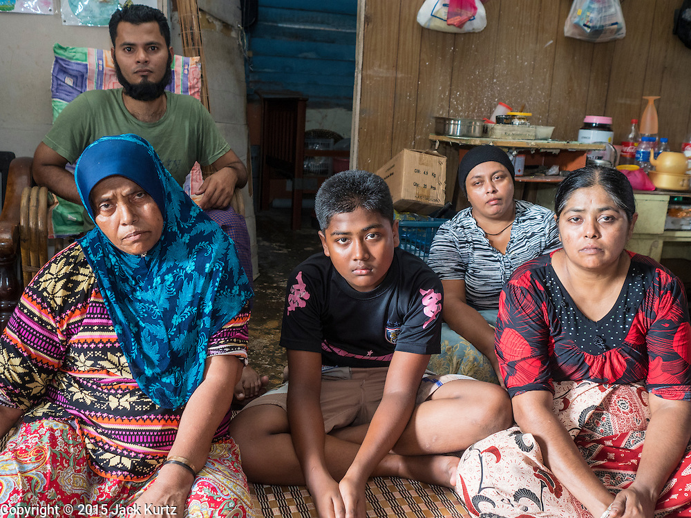 02 JUNE 2015 - KULAI, JOHORE, MALAYSIA:  A Rohingya refugee family from Sittwe, Myanmar, in their home in Kulai, Malaysia. None of them has official UNHCR refugee status, they face daily harassment from Malaysian police. They pay about 400 Malaysian Ringgit (about $110 US) a month rent for their home, which has numerous holes in the roof and exterior walls and floods in the rainy season. The UN says the Rohingya, a Muslim minority in western Myanmar, are the most persecuted ethnic minority in the world. The government of Myanmar insists the Rohingya are illegal immigrants from Bangladesh and has refused to grant them citizenship. Most of the Rohingya in Myanmar have been confined to Internal Displaced Persons camp in Rakhine state, bordering Bangladesh. Thousands of Rohingya have fled Myanmar and settled in Malaysia. Most fled on small fishing trawlers. There are about 1,500 Rohingya in the town of Kulai, in the Malaysian state of Johore. Only about 500 of them have been granted official refugee status by the UN High Commissioner for Refugees. The rest live under the radar, relying on gifts from their community and taking menial jobs to make ends meet. They face harassment from Malaysian police who, the Rohingya say, extort bribes from them.    PHOTO BY JACK KURTZ