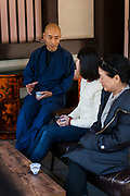 """Priest Matsumoto Shoukei drinking tea and talking with participants at a """"Temple Morning"""" cleaning session. Komyoji Temple, Kamiyacho, Tokyo, Japan, April 13, 2019. Matsumoto Shoukei is the author of A Monk's Guide to a Clean House and Mind (Penguin). He hold periodic cleaning sessions at his temple in Tokyo's Kamiyacho district."""