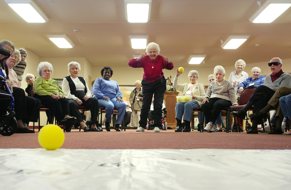 "Residents of The Worthington in Gahanna watch closely as Boston-native Sally WIlliams, center, tosses her final ball in modified indoor curling as part of the retirement community's ""2006 Olympic Challenge."" The games, which are being held all month, are intended to help residents get excercise and share some friendly competition. Williams placed second in the game."