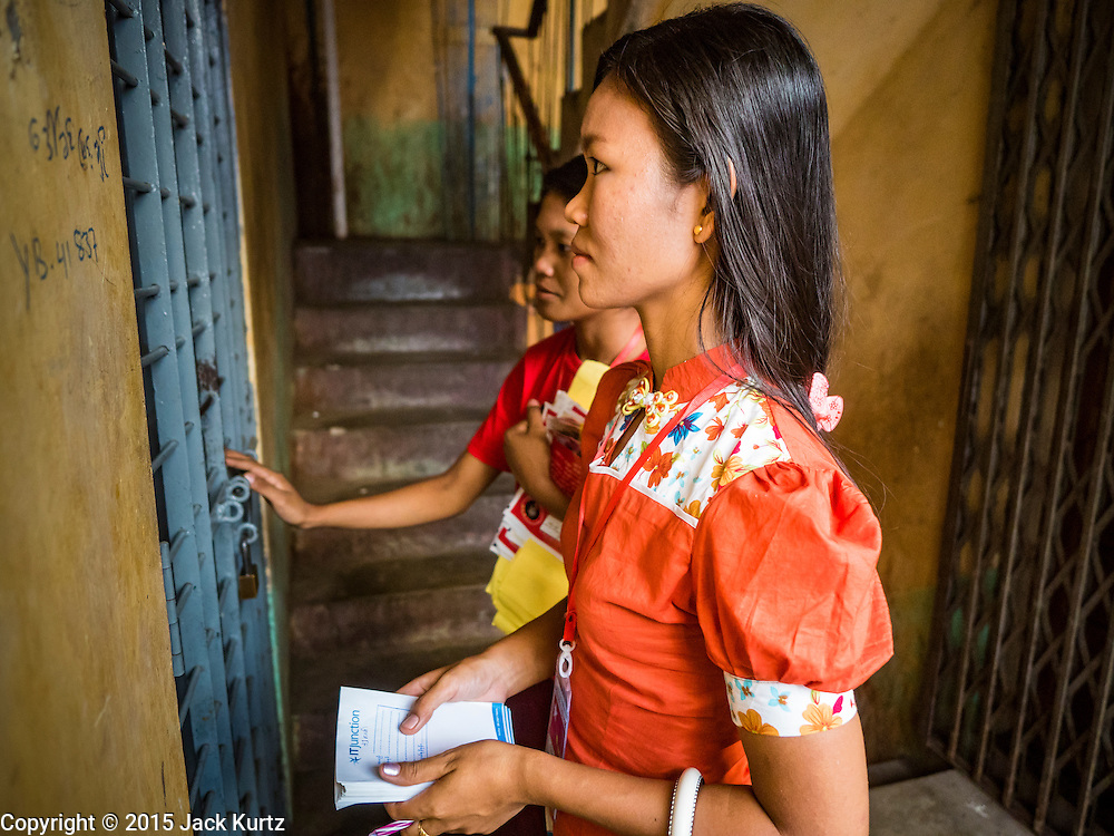 03 NOVEMBER 2015 - YANGON, MYANMAR:  NLD outreach workers go door to door in a Yangon tenement building during a voter outreach program. Political parties are wrapping up their campaigns in Myanmar (Burma). National elections are scheduled for Sunday Nov. 8. The two principal parties are the National League for Democracy (NLD), the party of democracy icon and Nobel Peace Prize winner Aung San Suu Kyi, and the ruling Union Solidarity and Development Party (USDP), led by incumbent President Thein Sein. There are more than 30 parties campaigning for national and local offices.       PHOTO BY JACK KURTZ