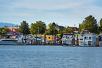 The Olympic Mountains are visible behind Fisherman's Wharf in Victoria, BC on a sunny summer day.