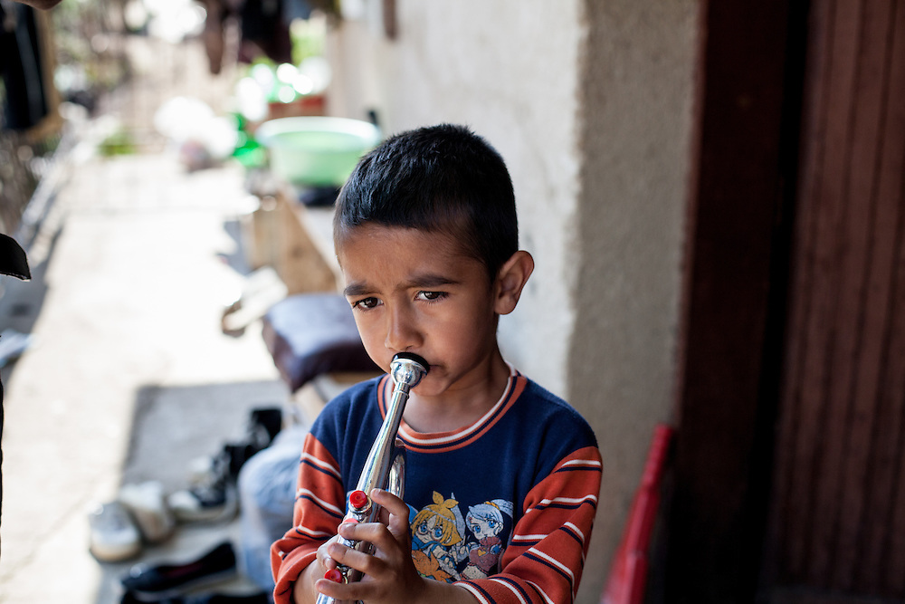 Child attending a spontaneous music session by a family and their neighbours on the streets of the Roma part in the city of Crnik, Macedonia.