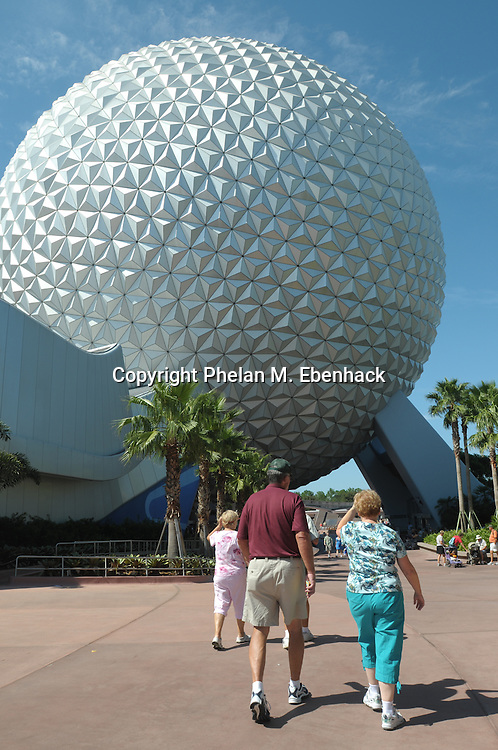 Tourists walk toward the Spaceship Earth ride at Walt Disney World's EPCOT theme park in Lake Buena Vista, Florida, Saturday, Sept. 27, 2008.
