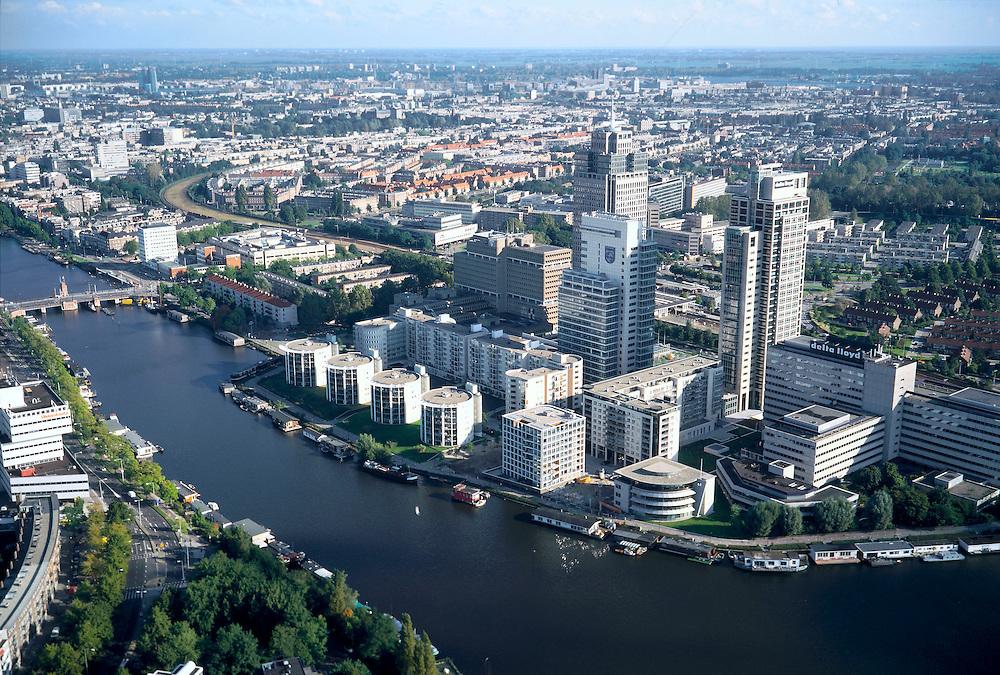 Nederland, Amsterdam,  Omval, 25-09-2002; Rembrandt, Mondriaan en Breitner torens langs rivier de Amstel, aan de Omval; dit gebied, met het hoofdkantoor Philips in de Breitner toren en daarnaast Delta Lloyd, vormt het begin van de Zuid-as; achter de kantoortorens het Amstelstation, aan het water stadsvilla's en woonboten; in vroeger tijden vormde de Omval een industriegebied; linksonder kantoorgebouw Rivierstaete aan de President Kennedylaan ('de Apenrots') woonarken, stadsvernieuwing, economie, bedrijvigheid, stadgezicht,  zie ook andere foto's van deze lokatie; Rembrandt, Mondriaan and Breitner towers along the Amstel River;  headquarter Philips in the Breitner tower as well as Delta Lloyd; the complex, marks the beginning of the South axis ('city' - financial district); behind office towers the river Amstel with water villas and houseboats, in earlier times was this an industrial area; residential parks, urban renewal, economics, business, economy, trade, activity, townscape, economics, business, city, offices;<br /> luchtfoto (toeslag), aerial photo (additional fee)<br /> foto /photo Siebe Swart