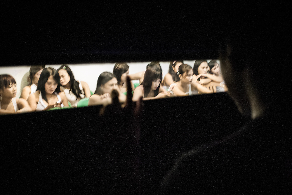 Seen through a one-way mirror, sex workers wait to be chosen by a customer inside Bar Kharisma, a popular brothel in Jayapura, the capital of Papua.<br />