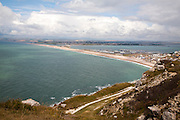 Chiswell village at the start of Chesil Beach with Weymouth harbour beyond, Isle of Portland, Dorset, England, UK