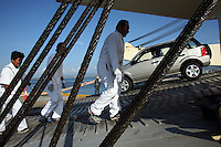 Workers unload cars form a cargo ship at the port of Manta, Ecuador on April 15, 2008. (Photo/Scott Dalton).