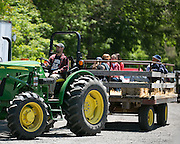 Stan Powers drives a hayride through his family's farm during the Paddle and Pour Festival in Pittsford on Saturday, May 23, 2015.