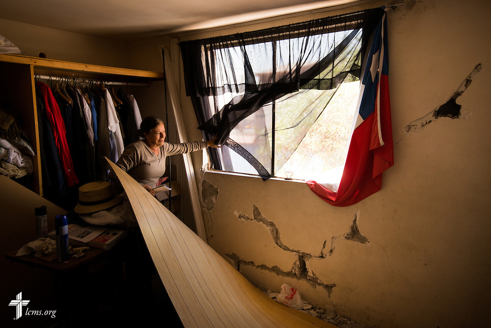 A woman displays the cracks in her wall on Wednesday, April 23, 2014, in Alto Hospicio, Chile. Her home was damaged by a magnitude 8.2 earthquake on April 1, 2014, that struck approximately 95km northwest of Iquique. The earthquake condemned several thousand homes and severely damaged more than 10,000 others. LCMS Communications/Erik M. Lunsford