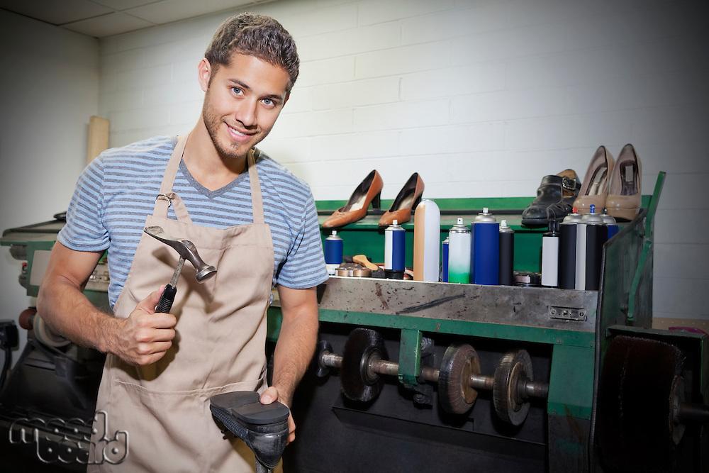 Young shoemaker hammering shoe sole in workshop