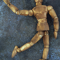 Dark stained wooden mannequin lying on tarnished metal sheet as if running skipping dancing or waving