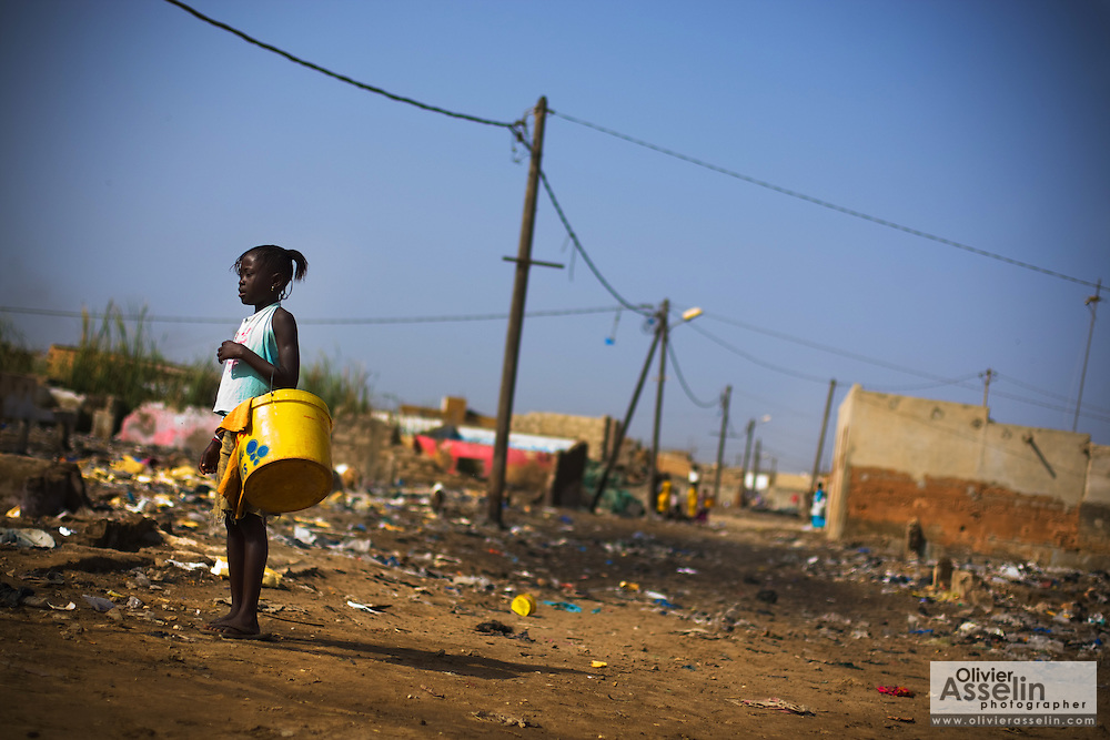 A girl stands on a dirt road in the Medina Gounass neighborhood of Guediawaye, Senegal on  Friday May 1, 2009. The entire area literally stands on packed garbage that was used as filler to raise the area that is prone to flooding during the annual rainy season. (Olivier Asselin for the New York Times).