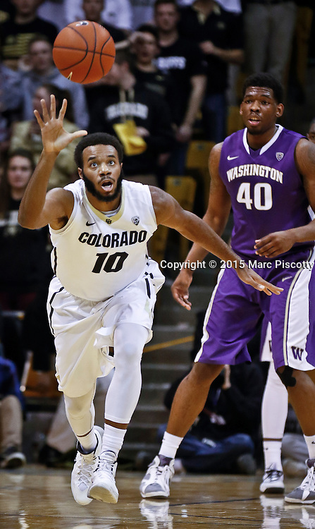 SHOT 1/22/15 9:12:29 PM - Colorado's Tre'Shaun Fletcher #10 chases after a loose ball in front of Washington's Shawn Kemp, Jr. #40 during their regular season Pac-12 basketball game at the Coors Events Center in Boulder, Co. Washington won the game 52-50 on a shot with less than a second to play in the game. (Photo by Marc Piscotty / © 2015)