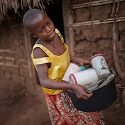 CAPTION: Juliet, who lives with a hearing impairment, cleans up her family home before preparing for school in the morning. SignHealth Uganda assists parents in understanding the nature of hearing impairment, which is traditionally seen as a bad omen on the family, and helps them to realise that hearing impaired children are still capable of leading normal, happy lives both at home and at school. The organisation has also helped Juliet by providing her with medical treatment to improve her hearing. LOCATION: Butenga Village, near Masaka City, Bukomansimbi District, Central Region, Uganda. INDIVIDUAL(S) PHOTOGRAPHED: Juliet Nassuna.