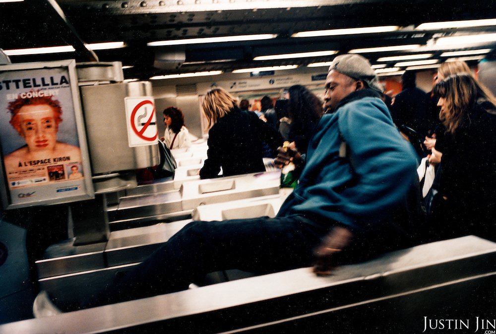 A fare-dodger leaps across a ticket gate in Paris' Republique metro.Picture taken 2005 by Justin Jin